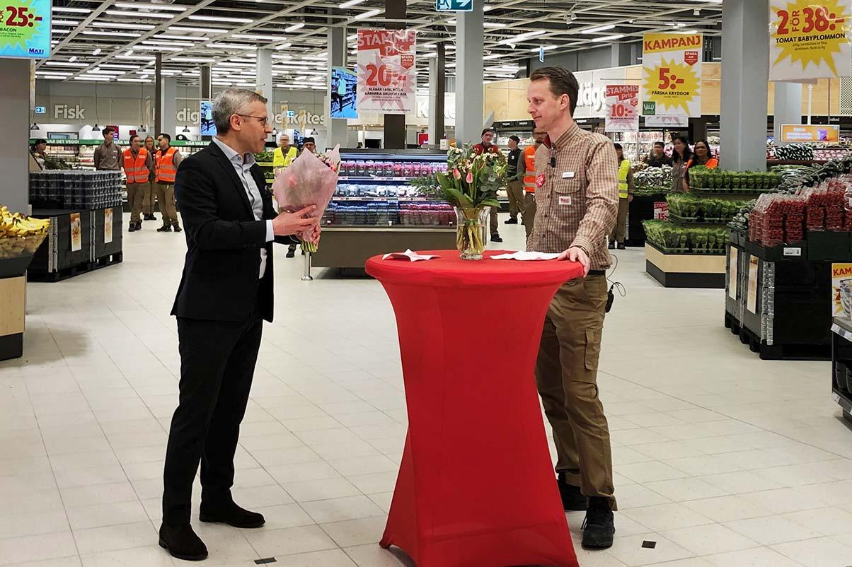 Andreas Lindelöf, NCC, räcker över en blomma till Gustaf Johansson, ICA. De båda står i en livsmedelsbutik.